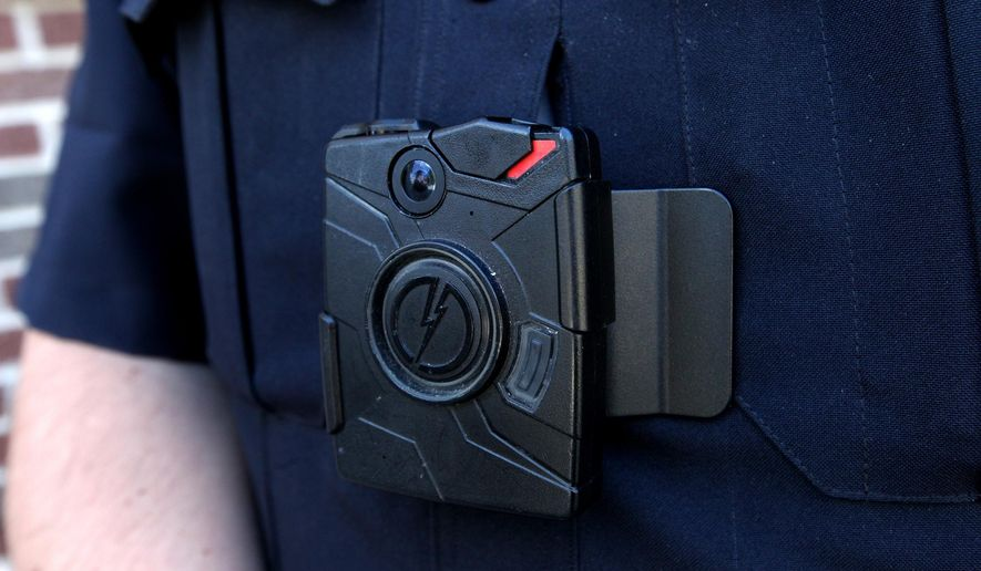 FILE- This Sept. 22, 2014 file photo shows a black camera clipped to a police uniform in Kent County, Mich. The police department in the western Michigan city of Lowell is among several around the state that are reporting positive results from the routine use of body video recorders for their officers. (AP Photo/Detroit Free Press, Jessica J. Trevino)  DETROIT NEWS OUT;  NO SALES