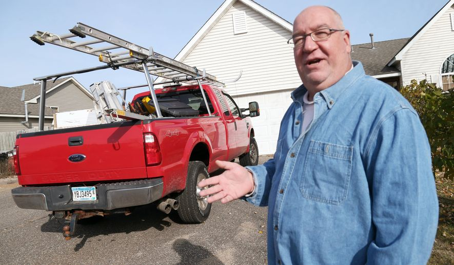 In this Oct. 24, 2014 photo,Tom Beckfeld, a self-employed snowplower and window cleaner, poses outside his home in Big Lake, Minn. Beckfeld acknowledged he's worried about getting a big rate increase notice from PreferredOne but added he has saved so much money thanks to the Affordable Care Act's ban on excluding patients with preexisting conditions that he'll be better off no matter what. (AP Photo/Jim Mone)