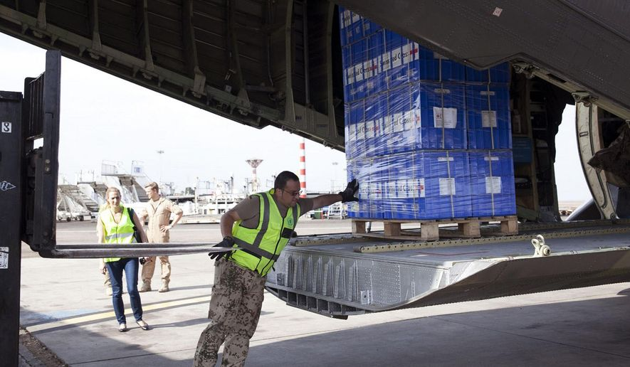 In this photo taken on Thursday, Oct. 23, 2014, a cargo plane is loaded with supplies to combat the spread of the Ebola virus in Accra, Ghana. Ghana, which is near the Ebola-hit countries of Liberia, Sierra Leone and Guinea but has not itself been exposed to the disease, has become the main staging area and headquarters for the U.N. Mission for Ebola Emergency Response, or UNMEER.  (AP Photo/Christian Thompson)