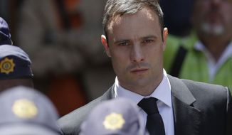 Oscar Pistorius is escorted by police officers as he leaves the high court in Pretoria, South Africa, in this Oct. 17, 2014, file photo. (AP Photo/Themba Hadebe, File)