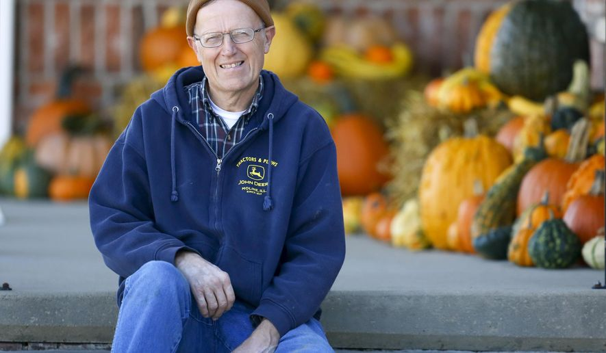 In a Tuesday, Oct. 21, 2014 photo, Lynn Sanders, of La Motte, Iowa, sits on the farm where he and his family grow pumpkins that he donates to his church, which sells them to benefit charities.  (AP Photo/Telegraph Herald, Mike Burley)