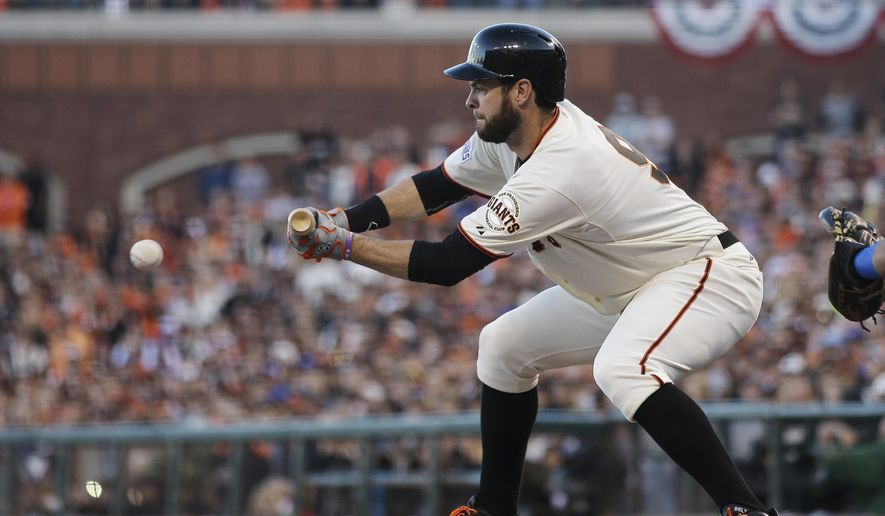 San Francisco Giants Brandon Belt bunts for a single during the second inning of Game 5 of baseball's World Series against the Kansas City Royals Sunday, Oct. 26, 2014, in San Francisco. (AP Photo/Matt Slocum)