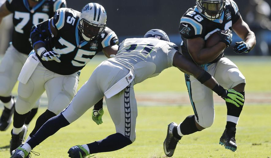 Carolina Panthers running back Jonathan Stewart (28) moves the ball as Seattle Seahawks strong safety Kam Chancellor (31) defends during the first half of an NFL football game, Sunday, Oct. 26, 2014, in Charlotte. (AP Photo/Chuck Burton)