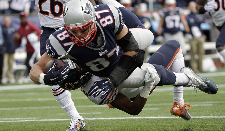 New England Patriots tight end Rob Gronkowski (87) carries Chicago Bears defensive back Al Louis-Jean (39) into the end zone while scoring a touchdown in the second half of an NFL football game on Sunday, Oct. 26, 2014, in Foxborough, Mass. (AP Photo/Steven Senne)