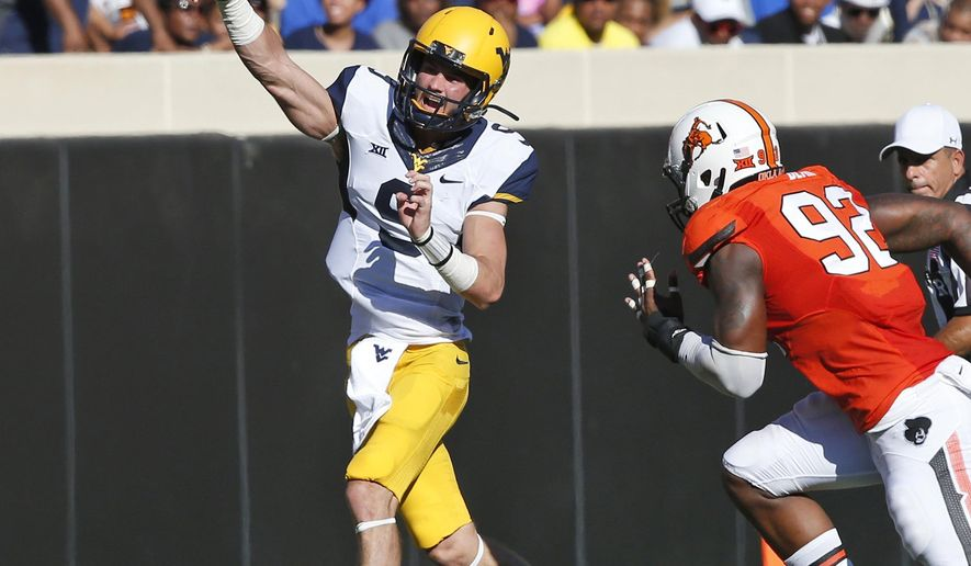 West Virginia quarterback Clint Trickett (9) passes under pressure from Oklahoma State defensive end Jimmy Bean (92) during the second quarter of an NCAA college football game in Stillwater, Okla., Saturday, Oct. 25, 2014. West Virginia won 34-10. (AP Photo/Sue Ogrocki)