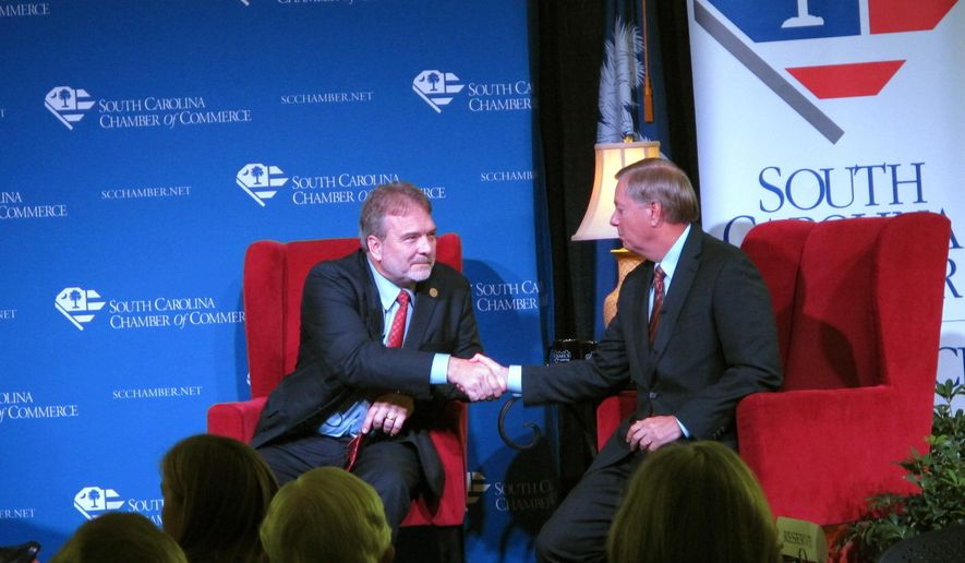 U.S. Sen. Lindsey Graham, right, and his Democratic challenger state Sen. Brad Hutto, left, shake hands after discussing the issues for the first time at a forum sponsored by the South Carolina Chamber of Commerce on Monday, Oct. 27, 2014, in Columbia, S.C. The two disagreed sharply on the issues at times, but kept it polite. (AP Photo/Jeffrey Collins)