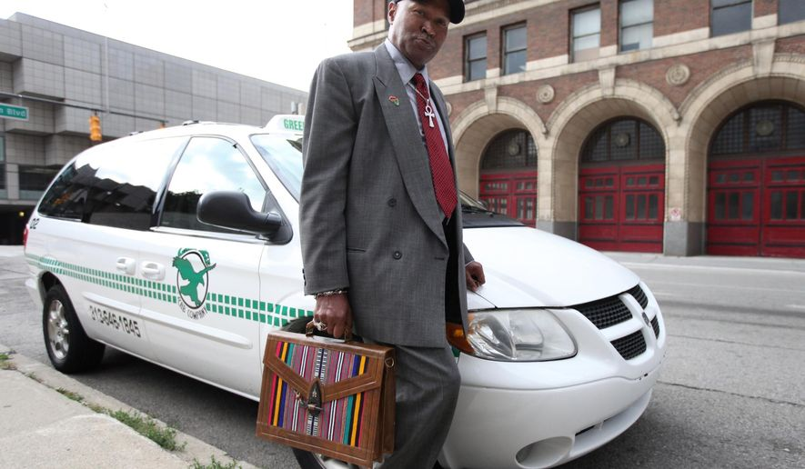 In a Wednesday, Oct. 15, 2014 photo, Metro Detroit Cab Drivers Association member Kenneth Kabaka Reynolds stands next to his Green Eagle cab that he drives, in Detroit. Detroit is looking to raise cab fares and possibly stop ride-sharing services such as Uber and Lyft ride from altering their rates to account for demand. (AP Photo/Detroit Free Press, Jessica J. Trevino)