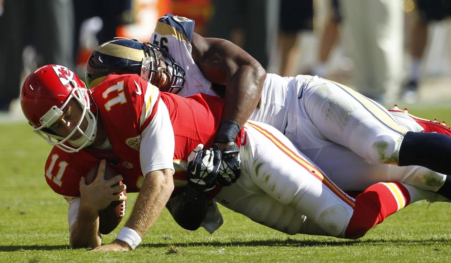 St. Louis Rams defensive end Robert Quinn (94) sacks Kansas City Chiefs quarterback Alex Smith (11) in the first half of an NFL football game in Kansas City, Mo., Sunday, Oct. 26, 2014. (AP Photo/Colin E. Braley)