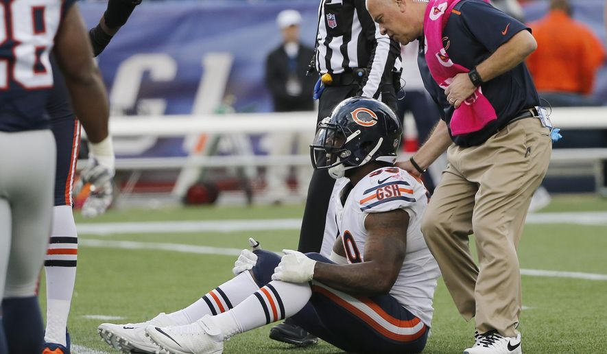 Chicago Bears defensive end Lamarr Houston, seated, receives attention after injuring his knee while celebrating a sack on New England Patriots backup quarterback Jimmy Garoppolo with about 3 minutes left in an NFL football game on Sunday, Oct. 26, 2014, in Foxborough, Mass. The Patriots won 51-23.  (AP Photo/Elise Amendola)