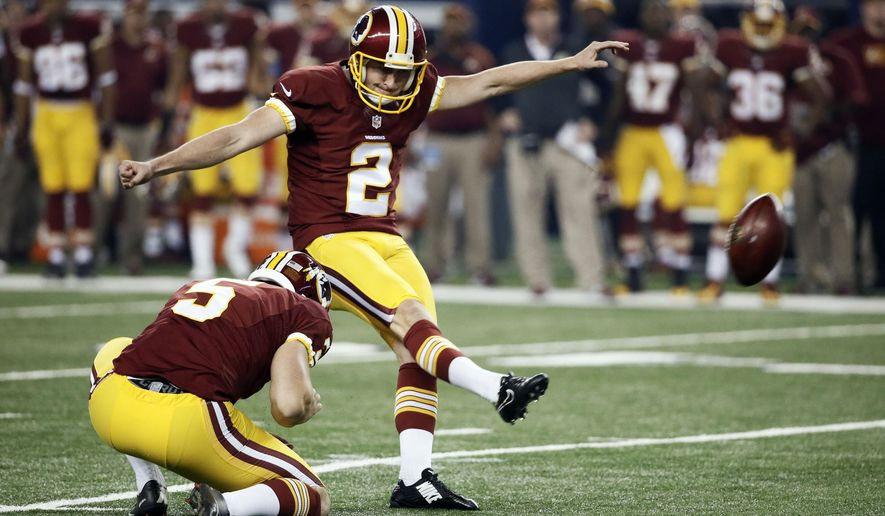 Washington Redskins punter Tress Way (5) holds as kicker Kai Forbath (2) kicks a field goal during the first half of an NFL football game against the Dallas Cowboys, Monday, Oct. 27, 2014, in Arlington, Texas. (AP Photo/Brandon Wade)