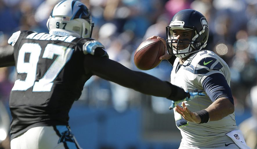 Seattle Seahawks quarterback Russell Wilson (3) works as Carolina Panthers defensive end Mario Addison (97) defends during the second half of an NFL football game, Sunday, Oct. 26, 2014, in Charlotte. (AP Photo/Bob Leverone)