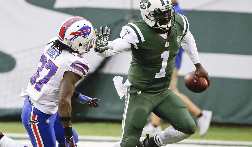 New York Jets quarterback Michael Vick (1) stiff arms Buffalo Bills' Nickell Robey (37) during the second half of an NFL football game, Sunday, Oct. 26, 2014, in East Rutherford N.J. The Bills won the game 43-23. (AP Photo/Seth Wenig)