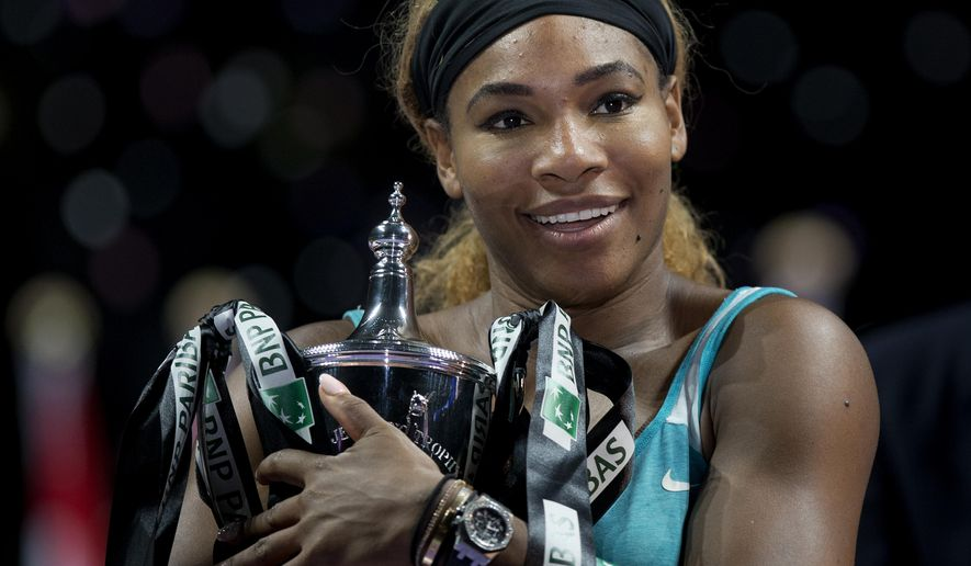 Serena Williams of the U.S. embraces her trophy after defeating Romania's Simona Halep in the singles final at the WTA tennis finals in Singapore, Sunday, Oct. 26, 2014. (AP Photo/Mark Baker)