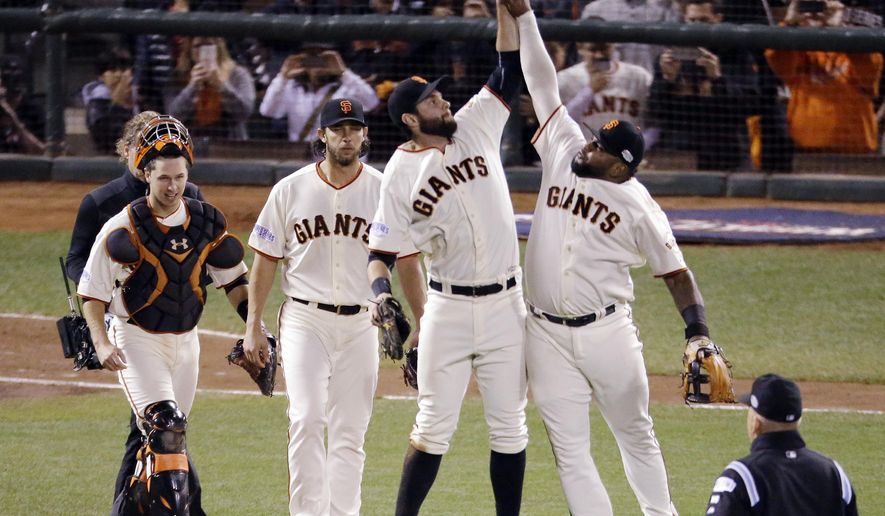 San Francisco Giants' Pablo Sandoval, right and Brandon Belt leap to high five as Buster Posey, left, and Madison Bumgarner walk off the field after the Giants beat the Royals 5-0 during Game 5 of baseball's World Series Sunday, Oct. 26, 2014, in San Francisco. The Giants beat the Royals 5-0 to lead the series 3-2. (AP Photo/Charlie Riedel)