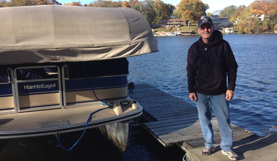 In this Saturday Oct. 25, 2014 photo, Bob Constable poses with with his pontoon boat, in Osceola, Ind. Constable is among more than a dozen Osceola residents who have had batteries and other items stolen from their boats in a crime spree dating back to at least Oct. 16. (AP Photo/South Bend Tribune, Christian Sheckler)