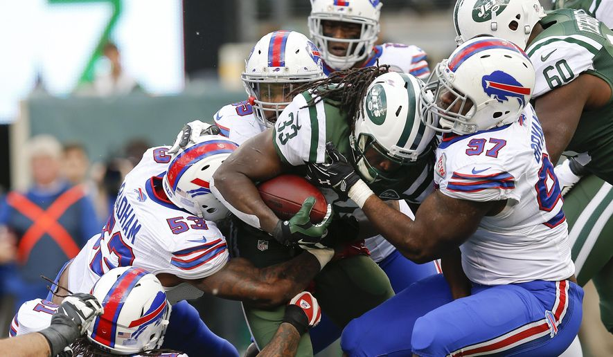 Buffalo Bills linebacker Ty Powell (57) and Nigel Bradham (53) tackle New York Jets' Chris Ivory (33) during the first half of an NFL football game, Sunday, Oct. 26, 2014, in East Rutherford, N.J.  (AP Photo/Kathy Willens)