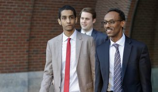 Robel Phillipos, left, a college friend of Boston Marathonbombing suspect Dzhokhar Tsarnaev, departs federal court with defense attorney Derege Demissie, right, following jury deliberations in his trial, Monday, Oct. 27, 2014, in Boston. Phillipos is accused of lying about being in Tsarnaev's dorm room three days after the deadly bombing, when two other friends removed a backpack containing fireworks and other potential evidence. (AP Photo/Steven Senne)