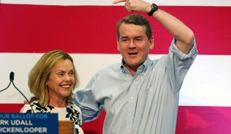 U.S. Sen. Michael Bennet, D-Colo., right, points to Democratic candidate for Colorado's secretary of state office, Betsy Markey, before former President Bill Clinton makes appearance at a high school in Aurora, Colo., to promote the state's Democratic candidates in the upcoming general election on Monday, Oct. 27, 2014. (AP Photo/David Zalubowski)