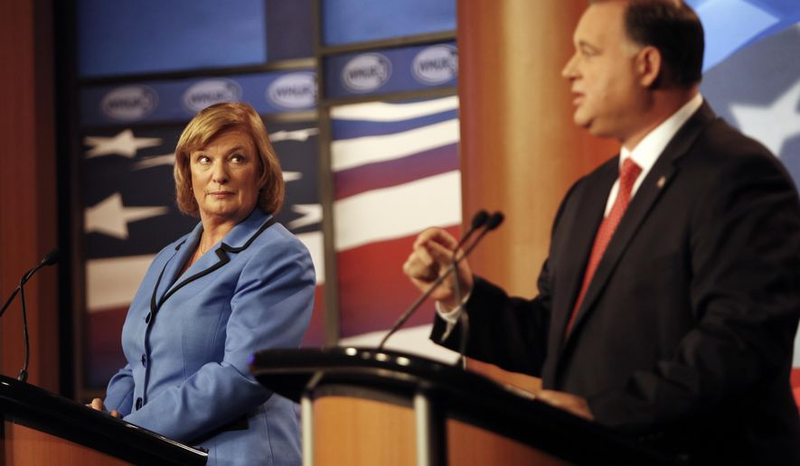 U.S. Rep. Carol Shea-Porter D-N.H., listens as, former Republican U.S. Rep. Frank Guinta,   answers a question during a live televised debate hosted by WMUR, the New Hampshire Union Leader, The New Hampshire Institute of Politics at Saint Anselm College in Manchester, N.H. Monday Oct. 27, 2014.  (AP Photo/Jim Cole)