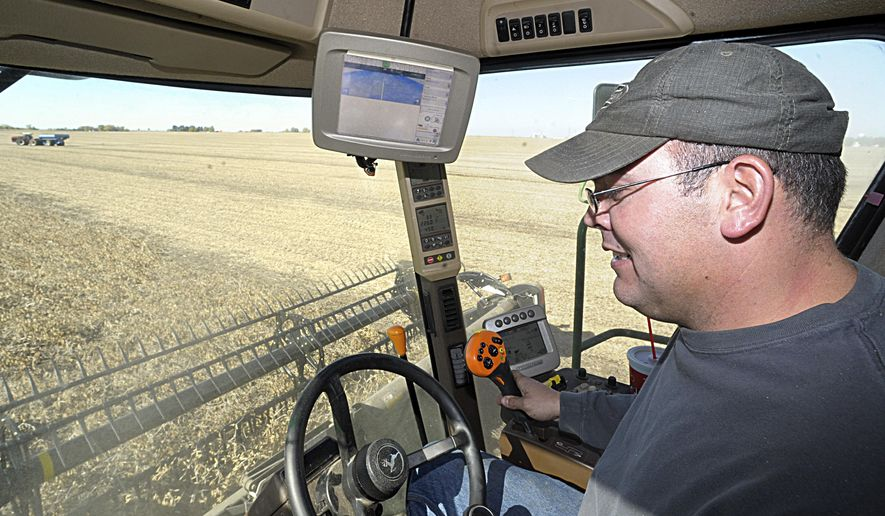 In this Oct. 22, 2014 photo, Luke Holly, of Granville, Ill., harvests a 120-acre soybean field in Ladd, Ill. His new farm equipment has high-tech equipment to help manage his yields. Holly's machines use field mapping data to automate planting in the spring and harvesting in the fall for his many fields from McNabb to Ladd. The auto-steering function on the machines helps save on fuel costs as well, he said, since only one pass over the area is needed. (AP Photo/NewsTribune, Scott Anderson)