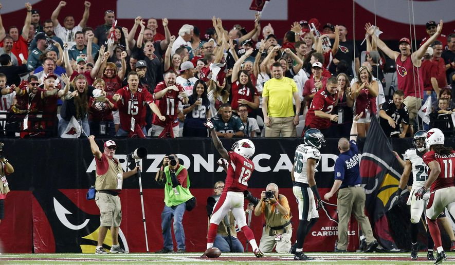 Arizona Cardinals' John Brown (12) celebrates his touchdown with fans as Cardinals' Larry Fitzgerald (11) looks on and Philadelphia Eagles' Cary Williams (26) walks away from the action during the second half of an NFL football game Sunday, Oct. 26, 2014, in Glendale, Ariz.  The Cardinals won 24-20. (AP Photo/Ross D. Franklin)