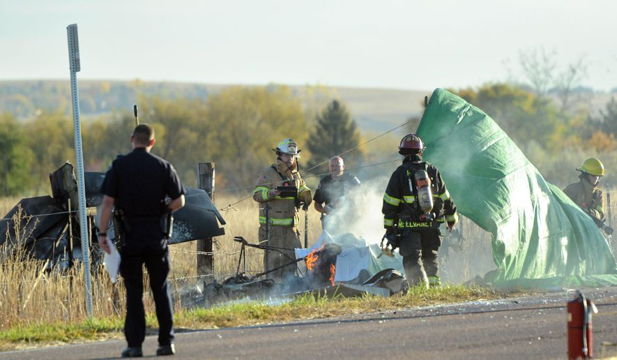 Emergency workers finish dousing a burning small plane after it crashed, leaving one person dead, just outside Boulder Municipal Airport, in Boulder, Colo., on Monday, Oct. 27, 2014. Boulder County Sheriff's Office Cmdr. Jeff Hendry said the crash occurred early Monday morning. He said the plane ended up in a ditch next to pastureland in a rural area north of Boulder. (AP Photo/The Daily Camera, Paul Aiken) NO SALES