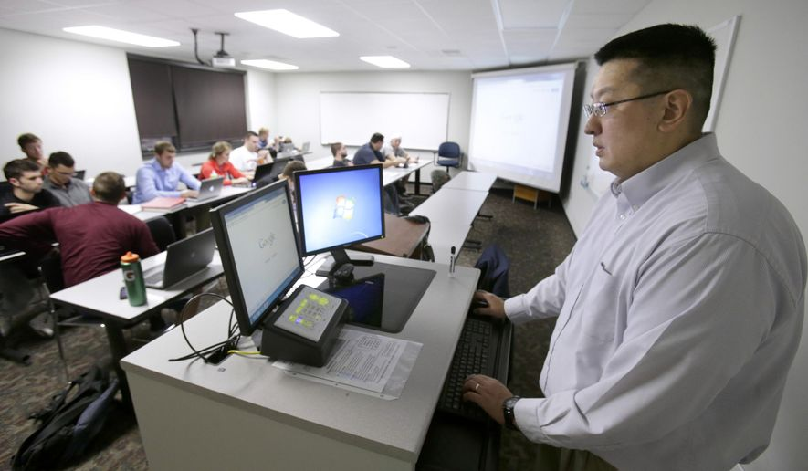Philip Kim conducts his class at Walsh University in North Canton, Ohio, Oct. 2, 2014. The assistant business professor is a high school dropout.  (AP Photo/The Repository, Scott Heckel)