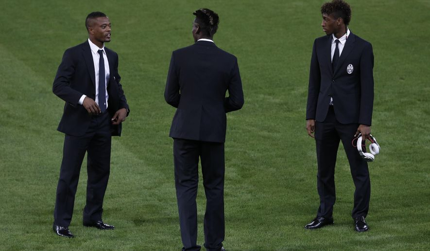 Juventus' Patrice Evra, left,  speaks with teammates Kingsley Coman, center, and Paul Pogba during a team visit at Georgios Karaiskakis stadium in the port of Piraeus near Athens, on Tuesday, Oct. 21, 2014. Juventus is going to face Olympiakos on Wednesday, Oct. 22, in a Champions League Group A soccer match. (AP Photo/Petros Giannakouris)