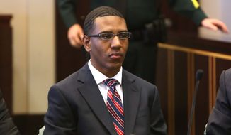 Dante Martin waits for jury selection Monday, Oct. 27, 2014, as he stands trial in Orange County, Fla. Martin is one of four members of Florida A&M University's marching band charged with manslaughter and felony hazing in the death of Robert Champion. His attorneys Dino Michaels, left, and Richard Escobar look on. The trials of three of four members of Florida A&M University's marching band on charges of felony hazing and manslaughter have been postponed until April. But the trial of Dante Martin began with jury selection Monday, nearly three years after drum major Robert Champion died from being beaten. (AP Photo/Orlando Sentinel, George Skene, Pool)