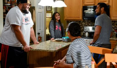 Washington Redskins practice squad offensive lineman Tevita Stevens, left, talks with his aunt, Venessa Fieeiki, second from right, and his two cousins, R.J., 17, right, and Charlotte, 13, second from left, at home as the Washington Redskins play monday night football against the Dallas Cowboys in Texas, Sterling, Va., Monday, October 27, 2014. (Andrew Harnik/The Washington Times)