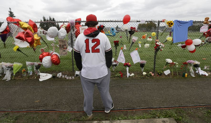 Brandon Bethers, 20, wears his Marysville Pilchuck High School baseball jersey as he views the growing memorial, Monday, Oct. 27, 2014, at the school in Marysville, Wash. On Friday, Oct. 24, 2014, student Jayson Fryberg opened fire in the school cafeteria, killing a fellow student and injuring others before taking his own life. A third student died Sunday night of her injuries.The school will be closed all week. (AP Photo/Ted S. Warren)