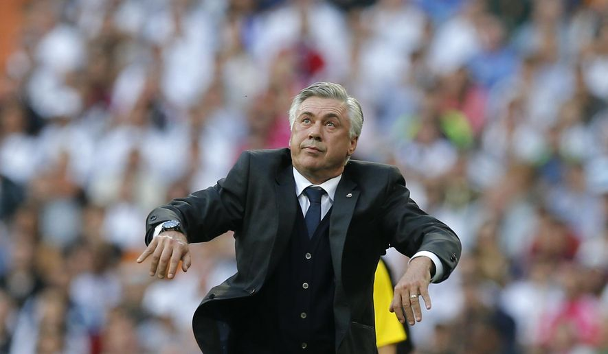 Real Madrid's coach Carlo Ancelotti watches the ball after throwing it back onto the field during a Spanish La Liga soccer match between Real Madrid and Barcelona at the Santiago Bernabeu stadium in Madrid, Spain, Saturday Oct. 25, 2014. (AP Photo/Paul White)