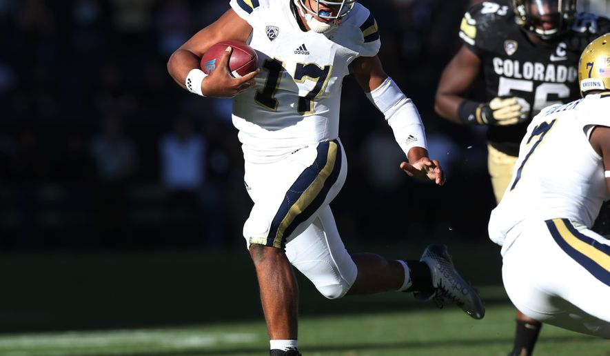 UCLA quarterback Brett Hundley, front, runs for a long gain as Colorado defensive lineman Juda parker trails in the second overtime of UCLA' 40-37 victory in double overtime in an NCAA football game in Boulder, Colo., on Saturday, Oct. 25, 2014. Hundley's run set the stage for his heroics when he scored the winning touchdown on the next play. (AP Photo/David Zalubowski)
