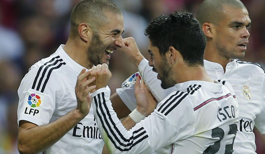 Real Madrid's Karim Benzema, left, celebrates with teammate Isco after scoring during a Spanish La Liga soccer match between Real Madrid and Barcelona at the Santiago Bernabeu stadium in Madrid, Spain, Saturday Oct. 25, 2014. (AP Photo/Paul White)