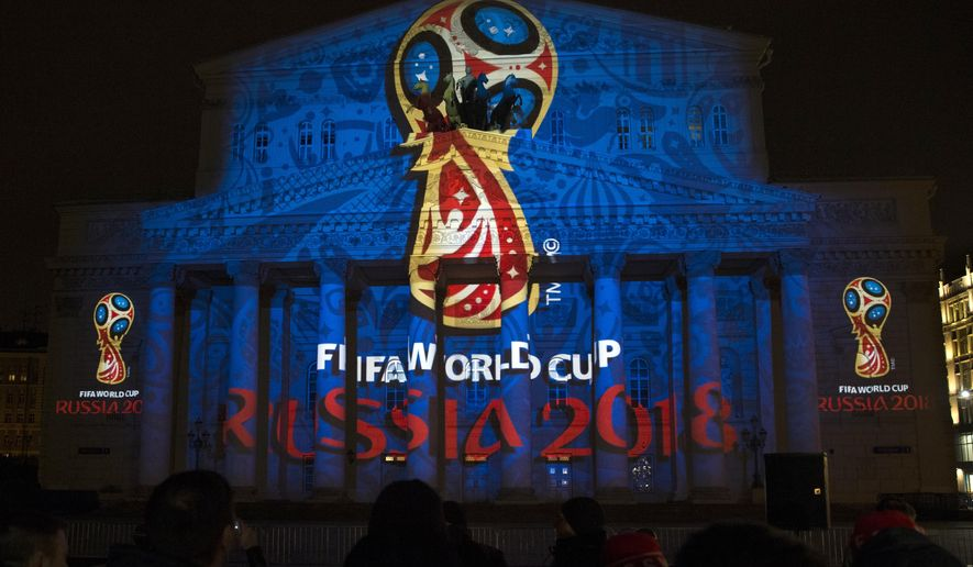 The official logo for the 2018 FIFA World Cup is presented on the facade of the Bolshoi Theatre in Moscow, Russia, Wednesday, Oct. 29, 2014. FIFA President Sepp Blatter has revealed the logo for the 2018 World Cup in Russia - with the help of a crew of cosmonauts. The logo depicts the World Cup trophy in red and blue, colors from the Russian flag, with gold trim. (AP Photo/Pavel Golovkin)