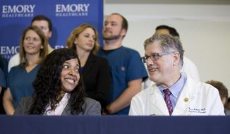 Amber Vinson, left, 29, the Dallas nurse who was being treated for Ebola, looks at Emory University Hospital epidemiologist Dr. Bruce Ribner, during a press conference after being discharged from the hospital, Tuesday, Oct. 28, 2014, in Atlanta. Vinson is now virus-free. (AP Photo/David Goldman)