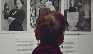 """A visitor read about cosmetic magnate Helena Rubinstein during a press preview of the exhibition """"Helena Rubinstein: Beauty is Power,"""" Tuesday Oct. 28, 2014 at the Jewish Museum in New York.  Also known as Madame, Rubinstein, who died in 1965,  collected African, Oceanic and Latin American art along with commissioned paintings of herself and drawings by Picasso. The exhibition opens Oct. 31 and runs through March 22 next year.   (AP Photo/Bebeto Matthews)"""