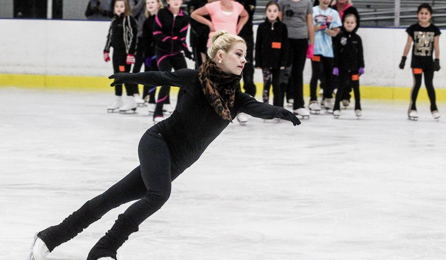 In this Monday, Oct. 27, 2014 photo, Olympic medalist Gracie Gold demonstrates a move for young skaters at the Crystal Lake Ice House in Crystal Lake, Ill.. Gold, whose Wagon Wheel Figure Skating Club is based in Crystal Lake, spent more than an hour on the ice with the young skaters, teaching them techniques and offering encouragement. Gold, a former Springfield resident, was in town for the Skate America competition. (AP Photo/Northwest Herald, Sarah Nader)  MANDATORY CREDIT