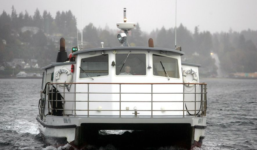 Admiral Pete passenger ferry captain Bill Nearhoff pilots the ship into the Bremerton dock on a gray wet morning.  He has been piloting the little ferries across Sinclair Inlet since 1961. (AP Photo/Kitsap Sun, Larry Steagall)
