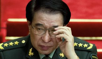 In this March 11, 2012 photo, Xu Caihou, then deputy chairman of the CPC Central Military Commission, which controls China's military adjusts his glasses during a plenary session of the National People's Congress at the Great Hall of the People in Beijing, China. Chinese prosecutors have indicted the former top military leader on bribery charges, state media said Tuesday, Oct. 28, 2014. (AP Photo/Andy Wong)