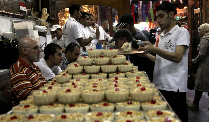Waiters prepare deserts in Bekdash, an ice-cream shop considered to make the finest Levantine gelato in the ancient bazaar known as the Hamdiyeh souq, in Damascus, Syria, Monday, Oct. 27, 2014. On Monday the lack of customers was palpable. Instead of the lines of people who once queued outside for a vanilla-flavored cone, the shop was only half-full. The knock-on effects of the latest fuel price rise and continued bombings have already shown in the price of bread, yogurt and milk. (AP Photo/Diaa Hadid)