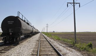 This May 14, 2013, file photo shows train cars on the tracks that run alongside a 250-acre field where Cronus Chemicals plan to build a $1.4 billion fertilizer plant just outside Tuscola , Ill., a town about 20 miles south of Champaign. (AP Photo/David Mercer, File) ** FILE **