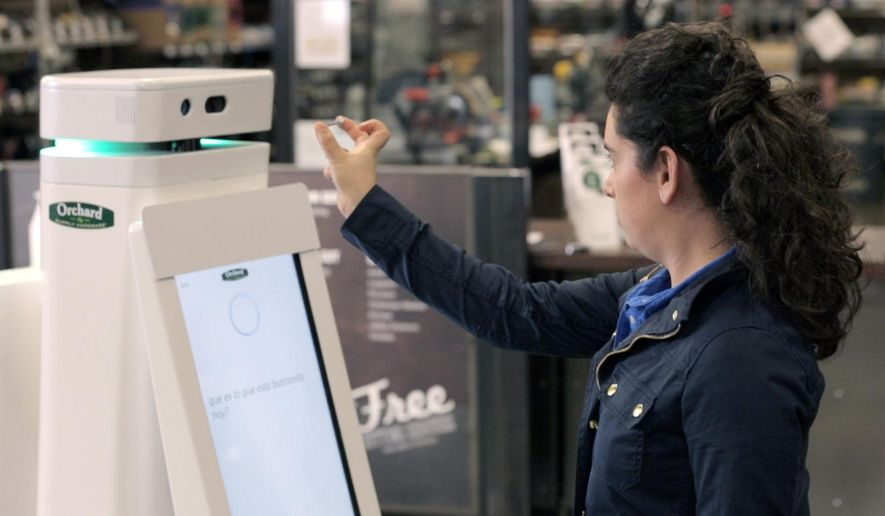 In this undated image provided by Lowe's, a woman holds a nail up to be scanned by an OSHbot robot. The robots are equipped with 3D cameras so they can scan and identify items. And customers can research items they want to buy on their screen. Then the robot can lead them to the aisle where an item is located. (AP Photo/Lowe's)