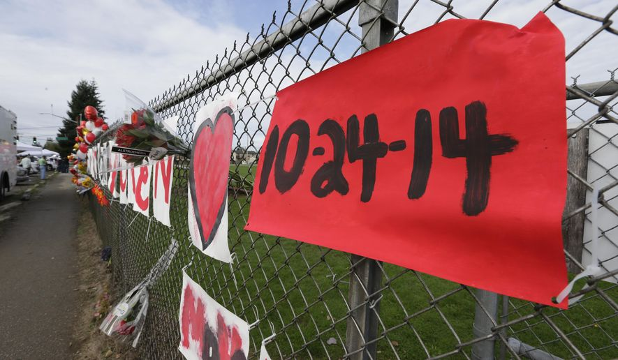 A sign bearing the Oct. 24, 2014 date of a shooting in the cafeteria of Marysville Pilchuck High School is shown Monday, Oct. 27, 2014 as part of a growing memorial on a fence around the school in Marysville, Wash. (AP Photo/Ted S. Warren)