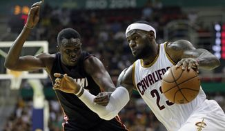 FILE - In this Oct. 11, 2014, file photo, Cleveland Cavaliers' LeBron James, right, drives past Miami Heat's Luol Deng during an NBA preseason basketball game as part of the NBA Global Games, in Rio de Janeiro, Brazil.  (AP Photo/Felipe Dana, File)