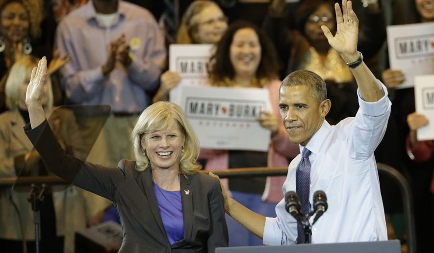President Barack Obama, right, campaigns for Wisconsin Democratic gubernatorial candidate Mary Burke during a rally at the North Division High School, Tuesday, Oct. 28, 2014, in Milwaukee. (AP Photo/Charles Rex Arbogast)