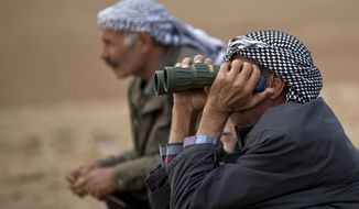 A man speaks on a cellphone while watching the town of Kobani during airstrikes by the US led coalition on the outskirts of Suruc, near the Turkey-Syria border, Tuesday, Oct. 28, 2014. Kobani, also known as Ayn Arab, and its surrounding areas, has been under assault by extremists of the Islamic State group since mid-September and is being defended by Kurdish fighters. (AP Photo/Vadim Ghirda)