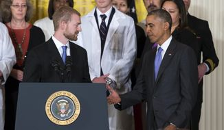 President Barack Obama shakes hands with Ebola survivor Dr. Kent Brantly during an event with American health care workers fighting the Ebola virus, Wednesday, Oct. 29, 2014, in the East Room of the White House in Washington. (AP Photo/Evan Vucci)