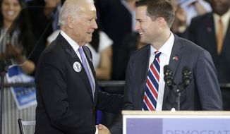 Vice President Joe Biden, left, and Democrat Seth Moulton, right, a candidate for the U.S. House of Representatives, shake hands as they take the stage during a campaign event for Moulton, Wednesday, Oct. 29, 2014, in Lynn, Mass. Moulton, an Iraq War veteran, is in a tight race with Republican Richard Tisei for the 6th U.S. House district north of Boston. (AP Photo/Steven Senne)