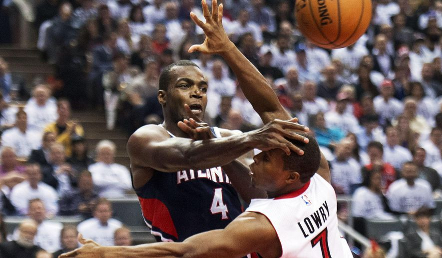 Toronto Raptors guard Kyle Lowry, right, battles for the ball against Atlanta Hawks forward Paul Millsap, left, during the first half of an NBA basketball game in Toronto on Wednesday, Oct. 29, 2014. (AP Photo/The Canadian Press, Nathan Denette)